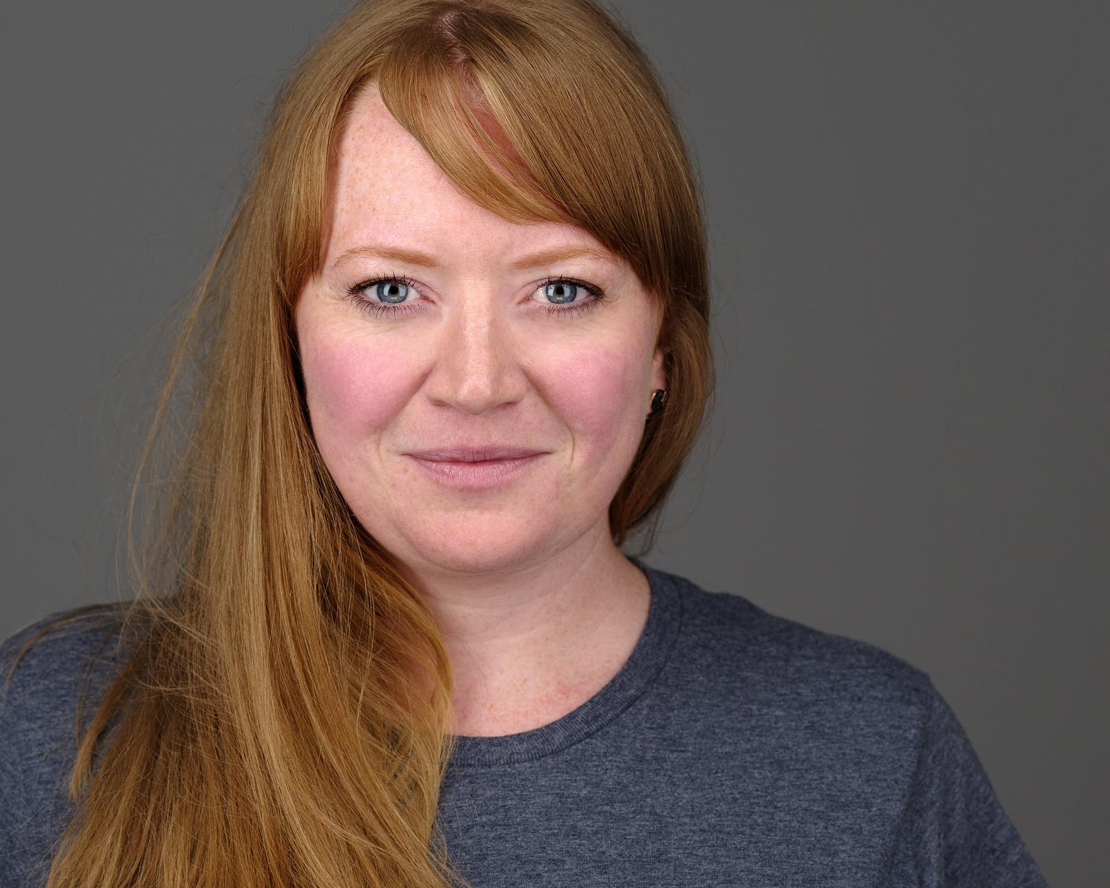Ein hochwertiges Bewerbungsfoto Headshot Portraitfoto Frau Porträt Porträtfoto Businessfoto lächelnd vor grauem Hintergrund